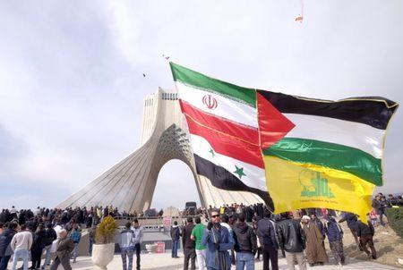 Man carries giant flag made of flags of Iran, Palestine, Syria and Hezbollah, during ceremony marking the 37th anniversary of the Islamic Revolution, in Tehran