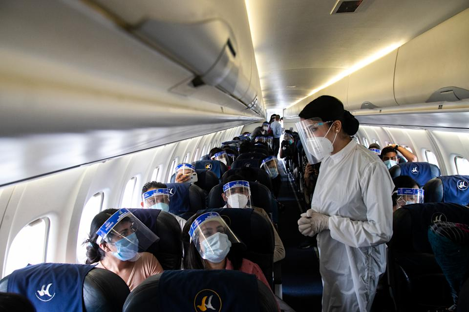 2020/06/25: An air hostess of Buddha Air wearing a protective suit attends to passengers inside the aircraft during a mock safety drill. (Photo by Prabin Ranabhat/SOPA Images/LightRocket via Getty Images)