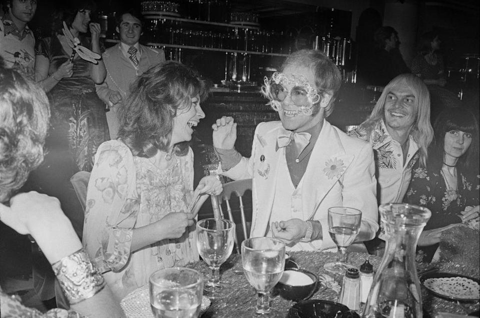 <p>Elton John amuses his fellow party guests, including actress Nanette Newman, at an event in 1974. </p>