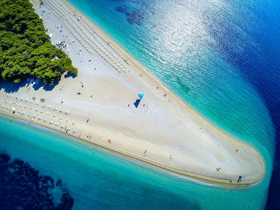 """Croatia has <a href=""""https://www.cntraveler.com/gallery/best-places-to-visit-in-croatia?mbid=synd_yahoo_rss"""" rel=""""nofollow noopener"""" target=""""_blank"""" data-ylk=""""slk:no shortage of beautiful beaches"""" class=""""link rapid-noclick-resp"""">no shortage of beautiful beaches</a>, but Zlatni Rat stands out for its striking and unusual shape (which actually changes depending on the current). Though it looks like a <a href=""""http://www.cntraveler.com/galleries/2016-04-19/the-most-beautiful-pink-sand-beaches-in-the-world?mbid=synd_yahoo_rss"""" rel=""""nofollow noopener"""" target=""""_blank"""" data-ylk=""""slk:golden sand beach"""" class=""""link rapid-noclick-resp"""">golden sand beach</a>, its shoreline is made up of smooth, tiny pebbles and stretches out for half a mile on either side of the tip. It's not just a place to lounge: Zlatni Rat is also a popular spot for windsurfing, jet-skiing, and stand-up paddle boarding."""