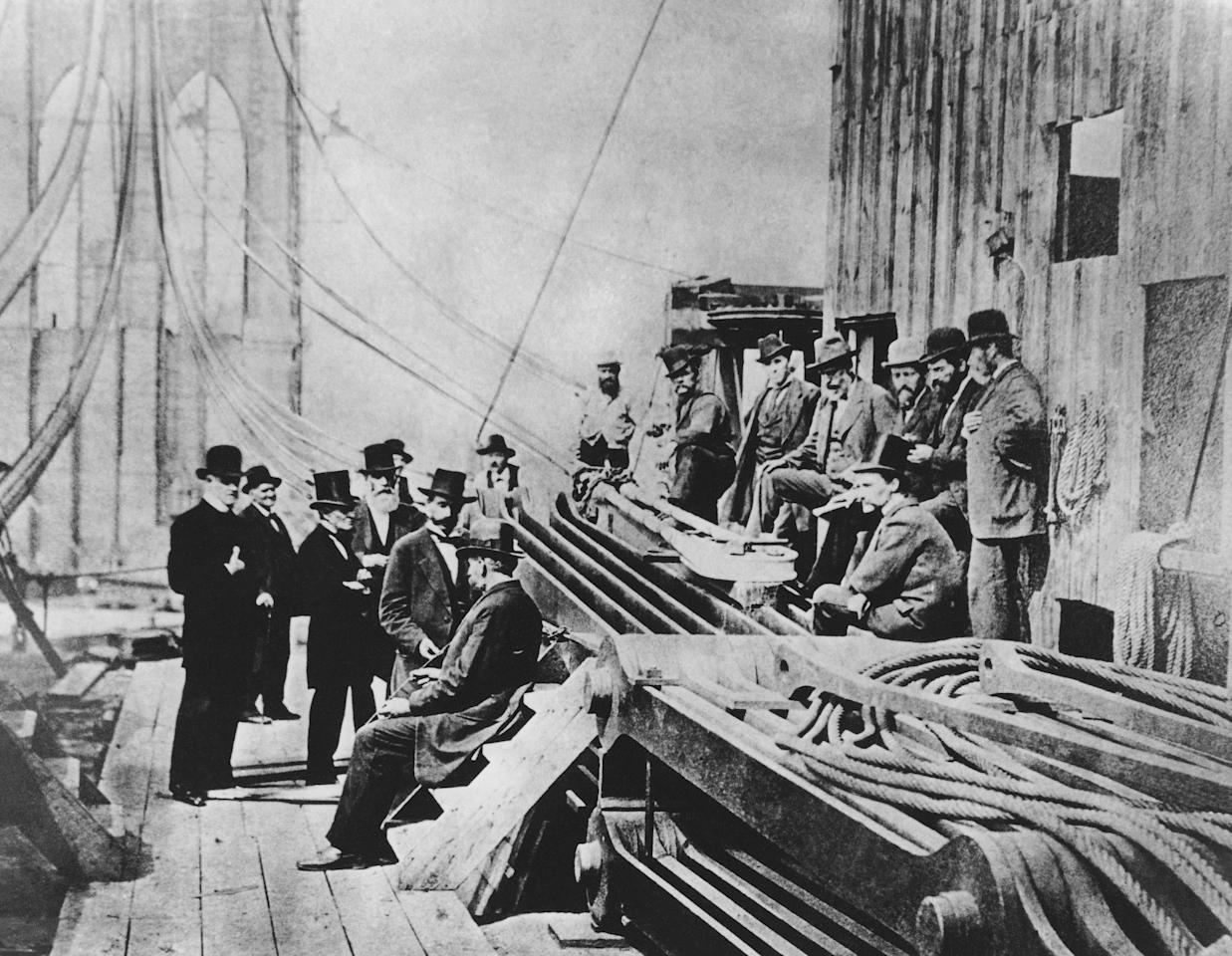 Officers of the New York and Brooklyn Corporation, and workmen, inspect the cable anchorage on the Brooklyn side of the Brooklyn Bridge during construction, Oct. 1878. (AP Photo)