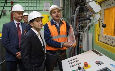 Volodymyr Zelenskiy, foreground, visits the 'new safe confinement' shelter over the remains of Chernobyl's reactor number four - Credit: Ukrainian Presidential Press Office via AP