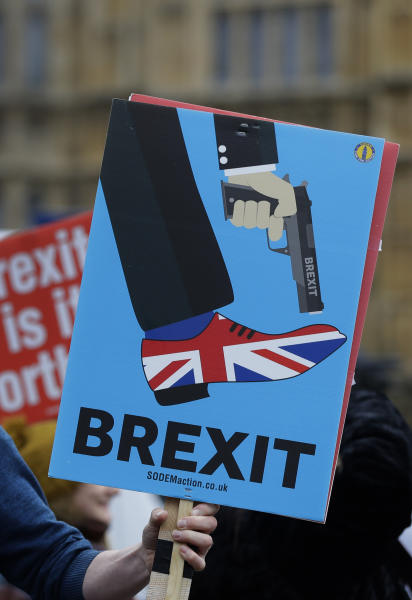 An anti-Brexit campaigner holds a banner in front of parliament in London, Wednesday, Dec. 5, 2018. Britain's Brexit debate has become a bruising battle between lawmakers and Prime Minister Theresa May's government. May is trying to keep her EU divorce deal on track Wednesday after her government was dealt a double blow by Parliament.(AP Photo/Kirsty Wigglesworth)