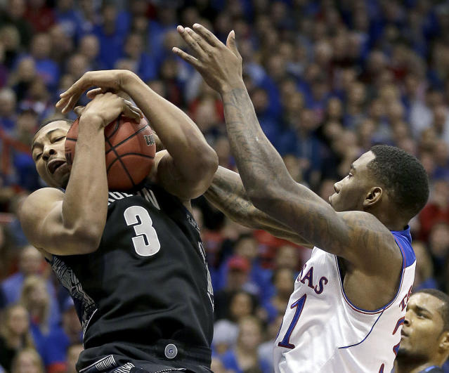 Kansas' Jamari Traylor, left, and Georgetown's Mikael Hopkins (3) battle for a rebound during the first half of an NCAA college basketball game Saturday, Dec. 21, 2013, in Lawrence, Kan. (AP Photo/Charlie Riedel)