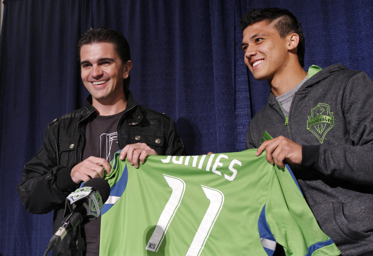 "Colombian singer Juanes, left, is given a Seattle Sounders FC jersey by forward Fredy Montero during a news conference about Juanes upcoming tour Tuesday, March 8, 2011, in Seattle. Juanes kicks-off his world ""P.A.R.C.E. Tour"" Thursday March 10, in Seattle."