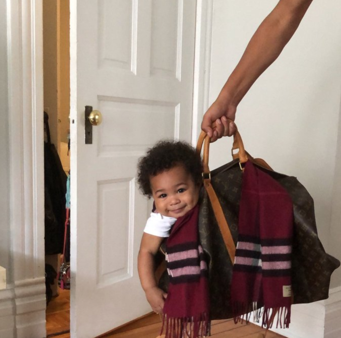 A photo of 9-month-old Lamar Jr., happily sitting in a purse is going viral. (Photo: Twitter/__Ily4)