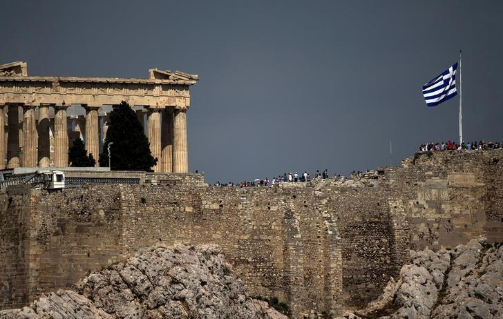 FILE PHOTO:A Greek flag flutters in front of the ancient Parthenon temple atop the Acropolis hill archaeological site in Athens
