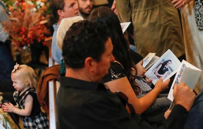 Relatives hold prayer pamphlets with a picture of Christina Marie Langford Johnson, who was killed by unknown assailants, during the funeral service before a burial at the cemetery in LeBaron, Chihuahua