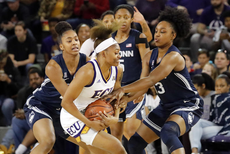 East Carolina's Necole Hope, center, gets tied up by Connecticut's Christyn Williams, right, and Aubrey Griffin, left, during the first half of an NCAA college basketball game, Saturday, Jan. 25, 2020 in Greenville, N.C. (AP Photo/Karl B DeBlaker)