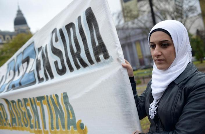 """A Syrian woman holds a sign reading """"Peace in Syria"""" at Mayo square in Buenos Aires, on September 7, 2013 (AFP Photo/Leo la Valle)"""