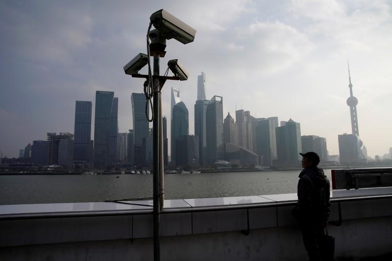 A man stands on the Bund in front of Shanghai's financial district of Pudong in Shanghai