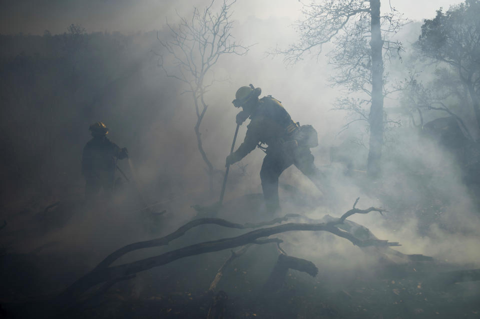 A firefighter extinguishes hotspots while battling the Olinda Fire in Anderson, Calif., Sunday, Oct. 25, 2020. The blaze was one of four fires burning near Redding that firefighters scrambled to stop as high winds buffeted Northern California. (AP Photo/Noah Berger)