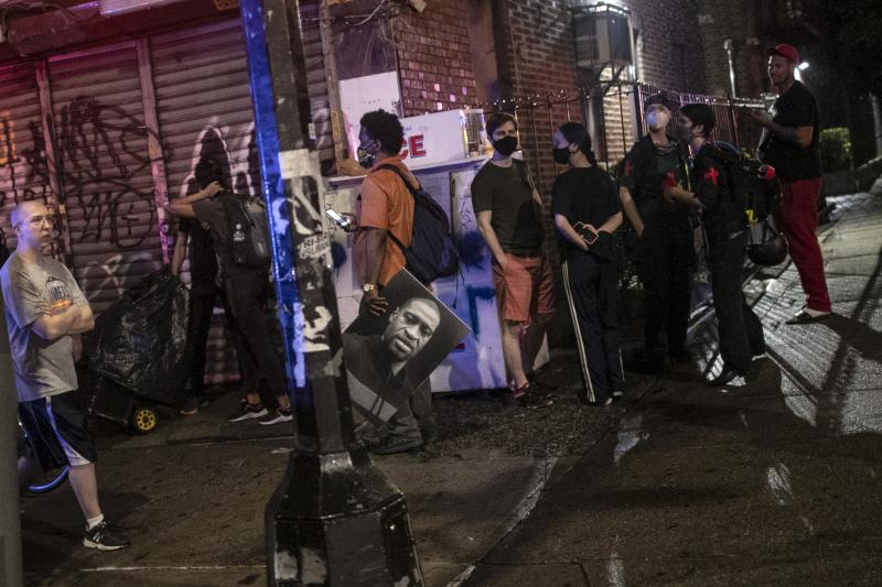 People watch as police arrest protesters for breaking a curfew during a solidarity rally calling for justice over the death of George Floyd, Friday, June 5, 2020, in the Brooklyn borough of New York. Floyd, an African American man, died on May 25 after a white Minneapolis police officer pressed a knee into his neck for several minutes even after he stopped moving and pleading for air. (AP Photo/Wong Maye-E)