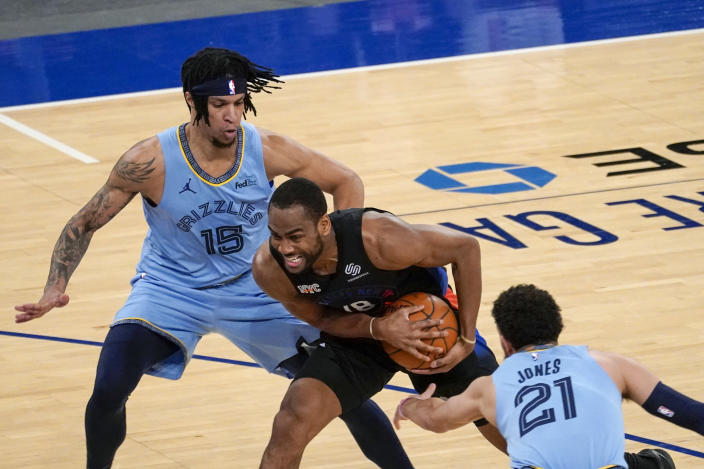 New York Knicks guard Alec Burks (18) drives against Memphis Grizzlies forward Brandon Clarke (15) and guard Tyus Jones (21) during the first half of an NBA basketball game Friday, April 9, 2021, at Madison Square Garden in New York. (AP Photo/Mary Altaffer, Pool)