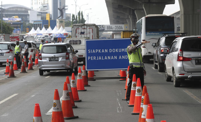 Indonesian police guard at a checkpoint during the imposition of large-scale restriction to curb the spread of the coronavirus on a toll road in Cikarang, West Java, Indonesia, Thursday, May 6, 2021. Indonesia is prohibiting travel during the popular homecoming period to celebrate Eid al-Fitr. The ban started Thursday and will last for 12 days, exempting only civil servants, police and military officers, and those who need to travel for work. (AP Photo/Achmad Ibrahim)