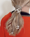 The coolest way to repurpose an old necklace or chain belt? Simply wrap it around the base of a low pony.