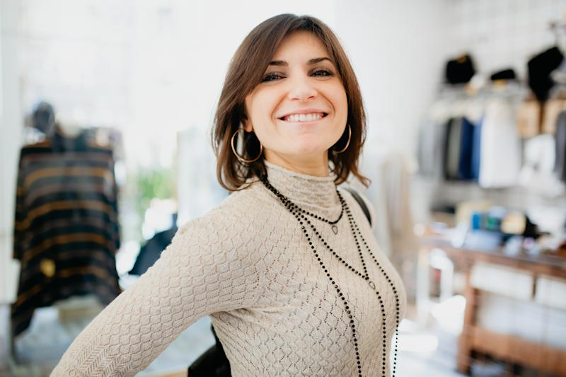 Woman showing off necklace in fashion boutique
