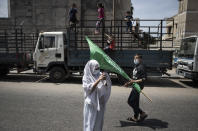 Palestinian children swing on the back of a truck as a young girl uses a mobile phone to photograph Hamas supporters protest in solidarity with Muslim worshippers in Jerusalem, in Gaza City, Friday, April. 23, 2021. (AP Photo/Khalil Hamra)