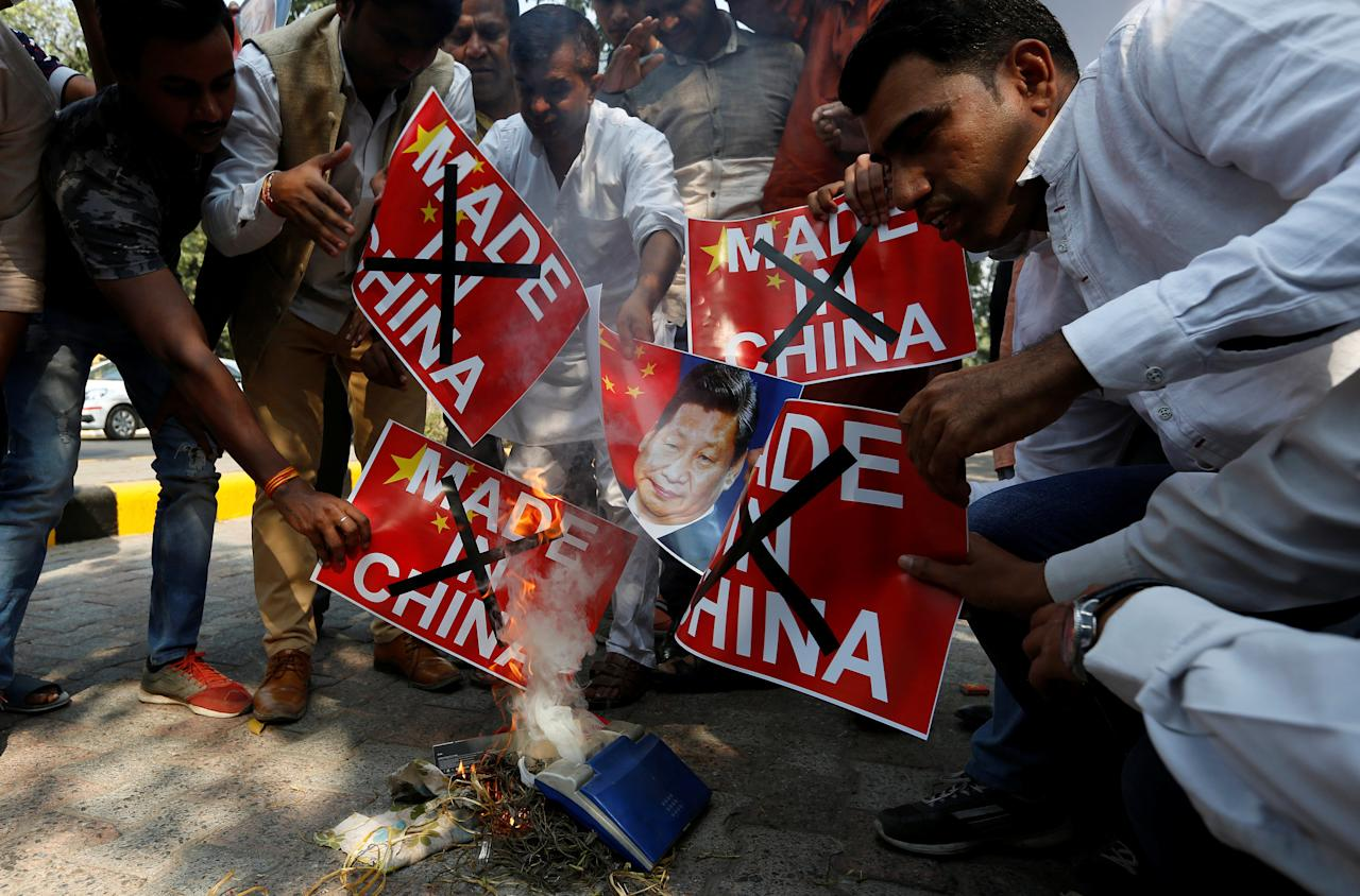 Demonstrators burn Chinese goods and poster of Chinese President Xi Jinping during a protest organised by the activists of Swadeshi Jagran Manch, a wing of the Hindu nationalist organisation Rashtriya Swayamsevak Sangh (RSS), as they demand the boycott of Chinese products, in New Delhi, India, October 26, 2016. REUTERS/Adnan Abidi