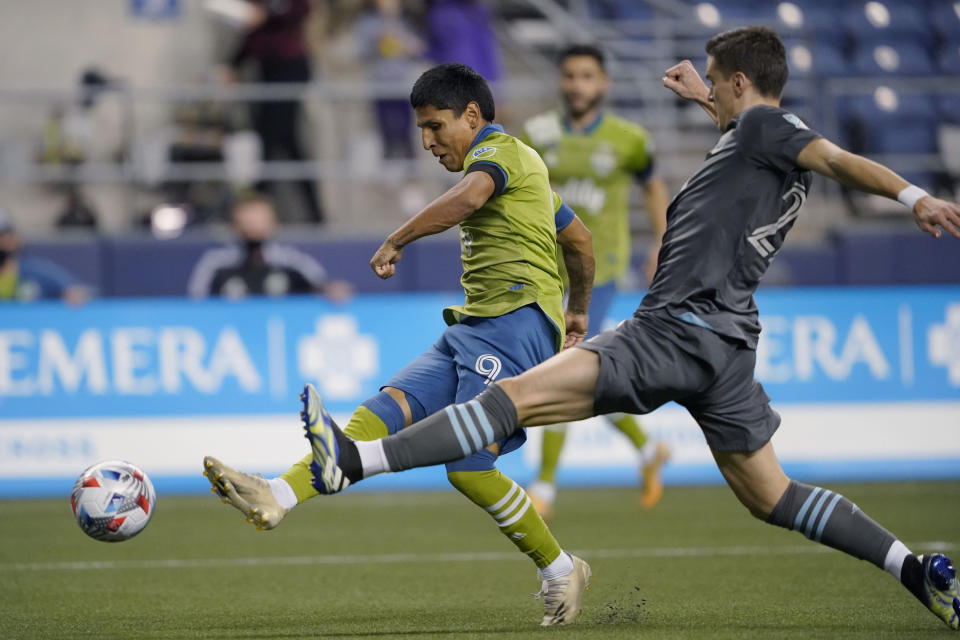 Seattle Sounders forward Raul Ruidiaz, left, kicks the ball next to Minnesota United defender Jukka Raitala, right, during the second half of an MLS soccer match Friday, April 16, 2021, in Seattle. The Sounders won 4-0. (AP Photo/Ted S. Warren)