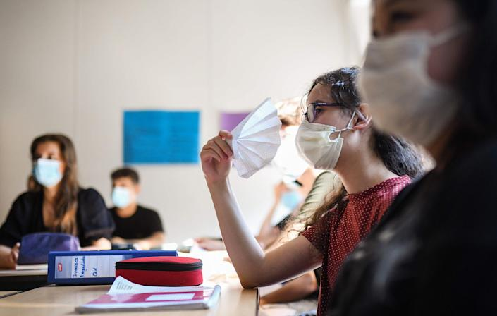 Image: Students of the eleventh grade sit with face masks in a classroom of the Phoenix high school in Dortmund, western Germany (Ina Fassbender / AFP - Getty Images)