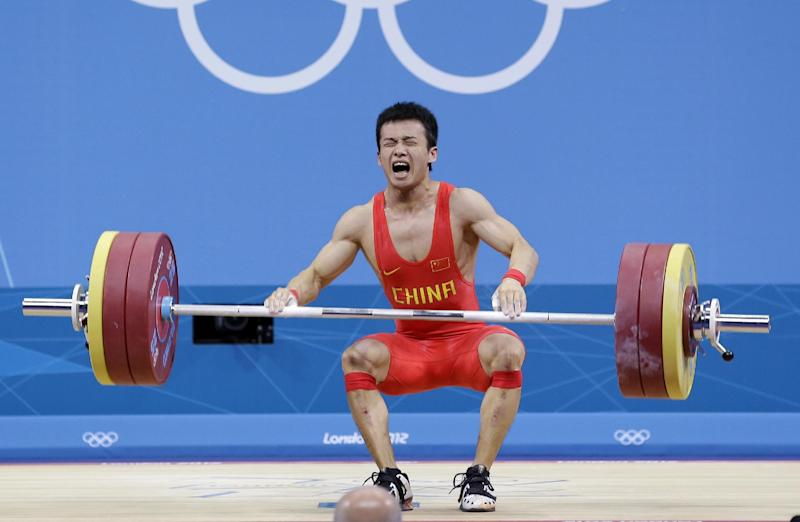 """In this Sunday, July 29, 2012 photo, Wu Jingbiao of China reacts after failing to complete his final lift and falling into silver position during the mens 56-kg, group A, weightlifting competition at the 2012 Summer Olympics in London. After the competiton, Wu lamented, """"I let my country down, I let the Chinese weightlifting team down; I let everyone who has cared about me down. I am sorry."""" (AP Photo/Hassan Ammar)"""