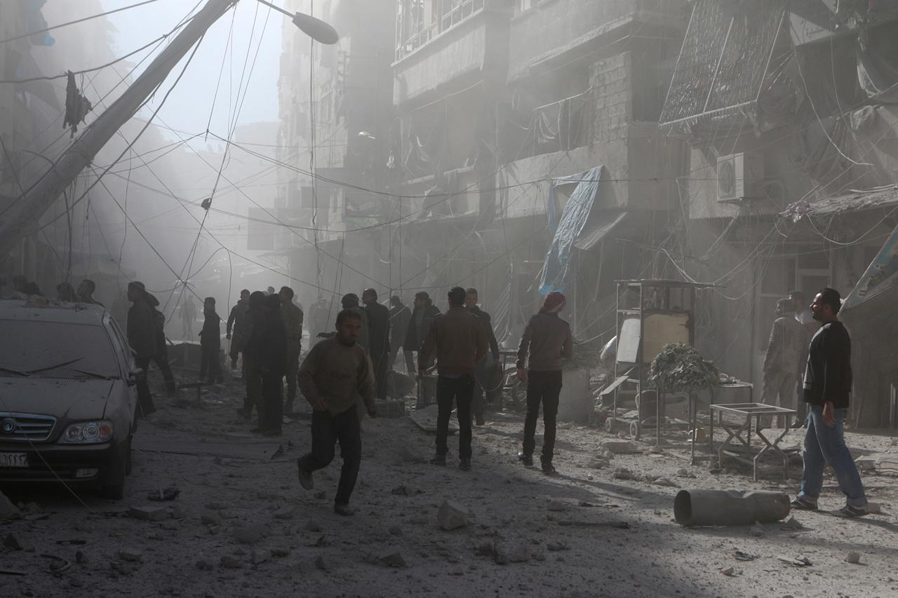 <p>People walk on the debris buildings after the war crafts belonging to the Assad Regime carried out airstrikes on residential areas at Firdevs neighborhood in Aleppo, Syria on Nov. 18, 2016. (Photo by Jawad al Rifai/Anadolu Agency/Getty Images) </p>