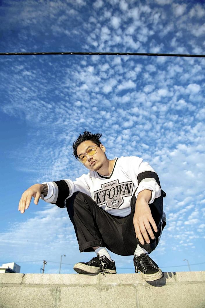 A man crouches on a cement wall with a sky full of clouds above him.