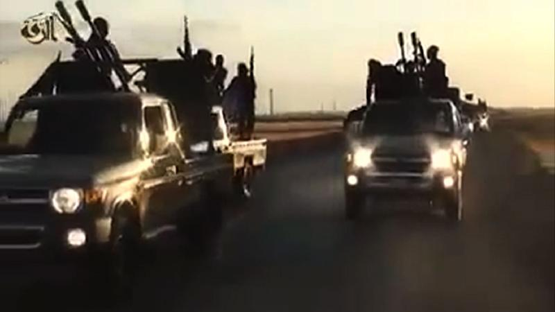An image grab from a video released by the Islamic State group's official Al-Raqqa site via YouTube allegedly shows IS recruits riding in armed trucks in an unknown location