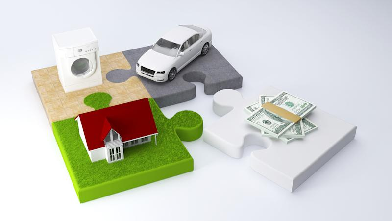 Three puzzle pieces with a car, washing machine and house are attached, while a fourth piece with a wad of money is detached.