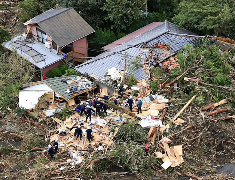 Rescue workers look for survivors as they stand on the rubble of a house buried by mudslides after a powerful typhoon hit Oshima on Izu Oshima island, about 120 kilometers (75 miles) south of Tokyo Wednesday morning, Oct. 16, 2013. Typhoon Wipha has lashed Japan, leaving at least seven people dead on a Pacific island south of Tokyo as it cut across the capital region and headed north. (AP Photo/Kyodo News) JAPAN OUT, CREDIT MANDATORY
