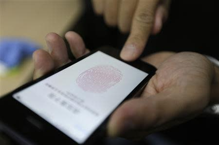 A journalist tests the the new iPhone 5S Touch ID fingerprint recognition feature at Apple Inc's announcement event in Beijing in this September 11, 2013 file photo. REUTERS/Jason Lee/Files
