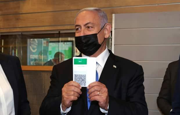 """Israeli Prime Minister Benjamin Netanyahu  holds a """"Green Pass"""" that allows citizens vaccinated against COVID-19 to access gyms, restaurants, bars and other locations in Israel."""
