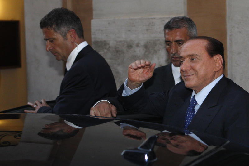 "Italian former Premier Silvio Berlusconi waves to reporters as he leaves after attending a meeting with the People of Freedom party's lawmakers at the Lower Chamber in Rome, Friday, Aug. 2, 2013. Italy's former premier, Silvio Berlusconi, for the first time in decades of criminal prosecutions related to his media empire was definitively convicted of tax fraud and sentenced to prison by the nation's highest court, Judge Antonio Esposito, in reading the court's decision Thursday, declared Berlusconi's conviction and four-year prison term ""irrevocable."" He also ordered another court to review the length of a ban on public office — the most incendiary element of the conviction because it threatens to interrupt, if not end, Berlusconi's political career. (AP Photo/Riccardo De Luca)"