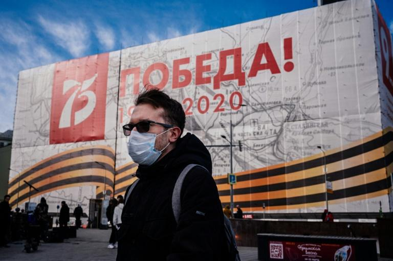 A man wearing a face mask against the spread of the coronavirus walks past a banner for the now much reduced 75th anniversary celebrations in Moscow marking the victory over Nazi Germany in World War II