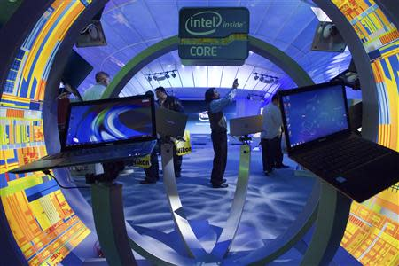 Gopi Sirineni (C) of San Jose, California takes a video of the Intel booth during the 2012 International Consumer Electronics Show (CES) in Las Vegas, Nevada, in this January 12, 2012 file photo. REUTERS/Steve Marcus/Files