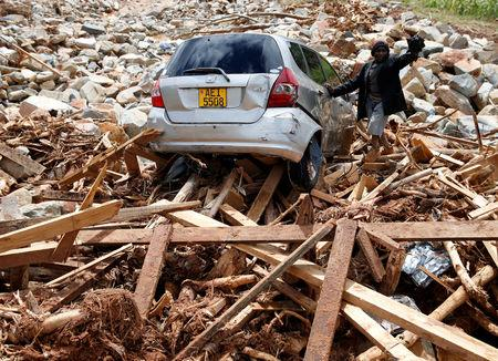A man gestures next to his car after it was swept into debris left by Cyclone Idai in Chimanimani, Zimbabwe, March 23, 2019. REUTERS/Philimon Bulawayo/Files