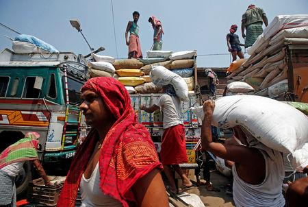 FILE PHOTO: Labourers carry sacks filled with sugar to load them onto a supply truck at a wholesale market in Kolkata