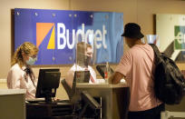 Plexiglass stands between patrons and staff at the car rental counter at Love Field airport Friday, May 28, 2021, in Dallas. (AP Photo/LM Otero)