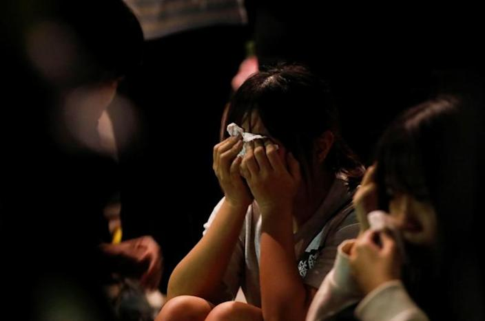 An anti-government demonstrator cries after surrendering at the campus of the Hong Kong Polytechnic University (PolyU), in Hong Kong