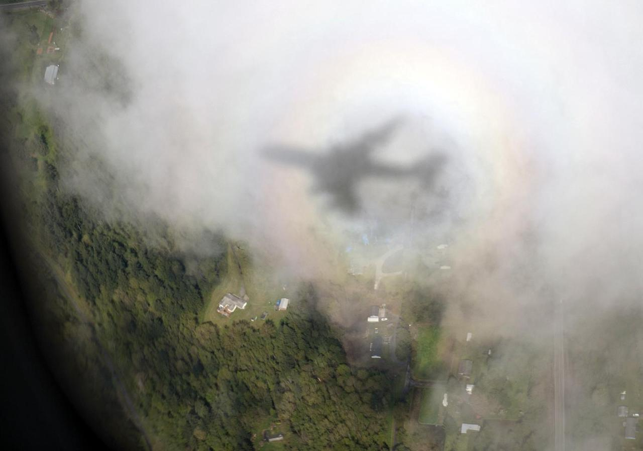 The shadow of Air Force One, with President Barack Obama aboard, is seen on a cloud as it approaches Paine Field Airport, Tuesday, April 22, 2014, in Everett, Wash., en route to Oso, Wash., the site of the deadly mudslide that struck the community in March. (AP Photo/Carolyn Kaster)