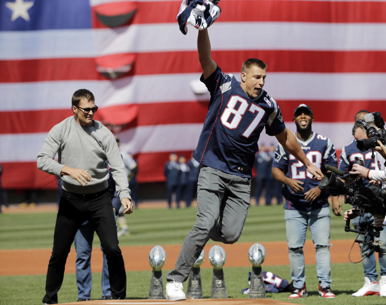 New England Patriots tight end Rob Gronkowski (87) runs with quarterback Tom Brady's, far left, recovered Super Bowl jersey as they joke around during Boston Red Sox home opening day ceremonies at Fenway Park, Monday, April 3, 2017, in Boston. The Red Sox face the Pittsburgh Pirates in the baseball game. (AP Photo/Elise Amendola)