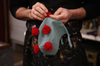 Venetian artisan mask maker Gualtiero Dall'Osto works on a carnival costume hat made to resemble the COVID-19 virus in his laboratory in Venice, Italy, Saturday, Jan. 30, 2021. Last year, with fear over the new coronavirus mounting, authorities abruptly shut down Venice Carnival on its third day, just before Italy became the first country in the West facing a outbreak. (AP Photo/Antonio Calanni)