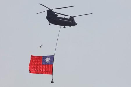 A helicopter carries a Taiwan national flag are seen during the National Day celebrations in Taipei