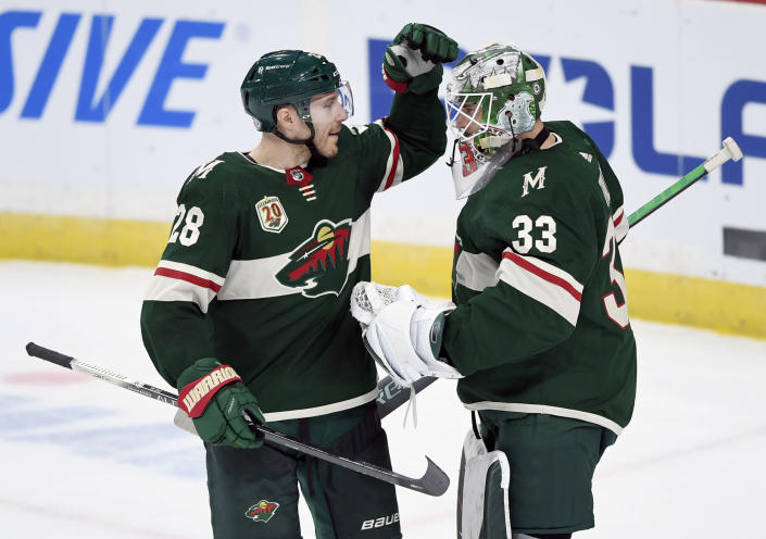 Minnesota Wild's Ian Cole (28) and goaltender Cam Talbot (33) celebrate a win against the Arizona Coyotes after an NHL hockey game Sunday, March 14, 2021, in St. Paul, Minn. (AP Photo/Hannah Foslien)