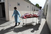 Afghan health workers carry the body of a woman who died from COVID-19 at the Afghan-Japan Communicable Disease Hospital in Kabul, Afghanistan, Sunday, May 30, 2021. Afghanistan is battling a brutal third wave of COVID infections, while health officials plead for vaccines, expressing deep frustration at the inequities of the global vaccine distribution. Positive COVID cases jump from eight percent to 60 per cent in some parts of the country. (AP Photo/Rahmat Gul)