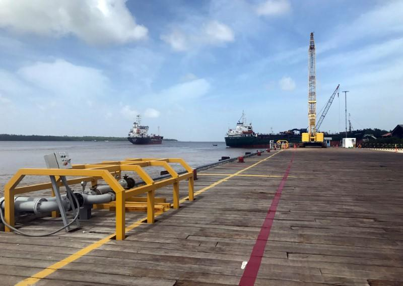 Vessels carrying supplies for an offshore oil platform operated by Exxon Mobil are seen at the Guyana Shore Base Inc wharf on the Demerara River south of Georgetown