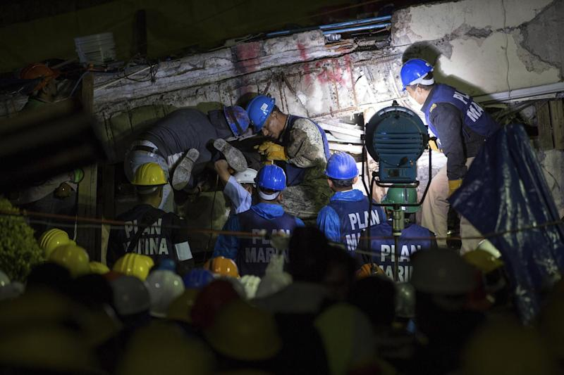 Search and rescue team members work to bring down a large piece of concrete during rescue efforts at the Enrique Rebsamen school in Mexico City: AP Photo/Anthony Vasquez