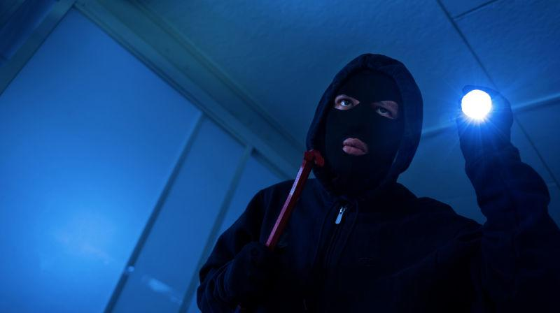 Thief breaking and entering with flashlight
