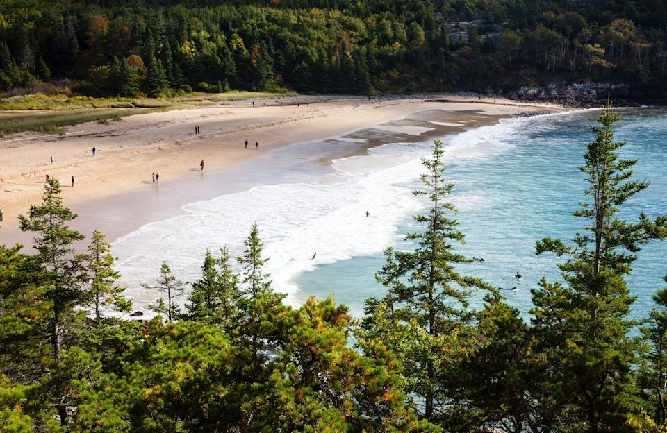 """<p>If peace and quiet are what you're looking for, don't miss the hidden gem that is Sand Beach in <a href=""""https://www.nps.gov/acad/index.htm"""" rel=""""nofollow noopener"""" target=""""_blank"""" data-ylk=""""slk:Acadia National Park,"""" class=""""link rapid-noclick-resp"""">Acadia National Park,</a> Maine. The <a href=""""https://acadiamagic.com/SandBeach.html"""" rel=""""nofollow noopener"""" target=""""_blank"""" data-ylk=""""slk:290-yard beach"""" class=""""link rapid-noclick-resp"""">290-yard beach</a> is secluded by a curtain of leafy green trees and is known for its unique sand made of shell fragments. Plus, you can combine your beach day with a hike along the <a href=""""https://acadiamagic.com/great-head-trail.html"""" rel=""""nofollow noopener"""" target=""""_blank"""" data-ylk=""""slk:Great Head Trail"""" class=""""link rapid-noclick-resp"""">Great Head Trail</a>, which weaves along nearby cliffs, offering a spectacular aerial <br> view of Sand Beach.<br></p>"""